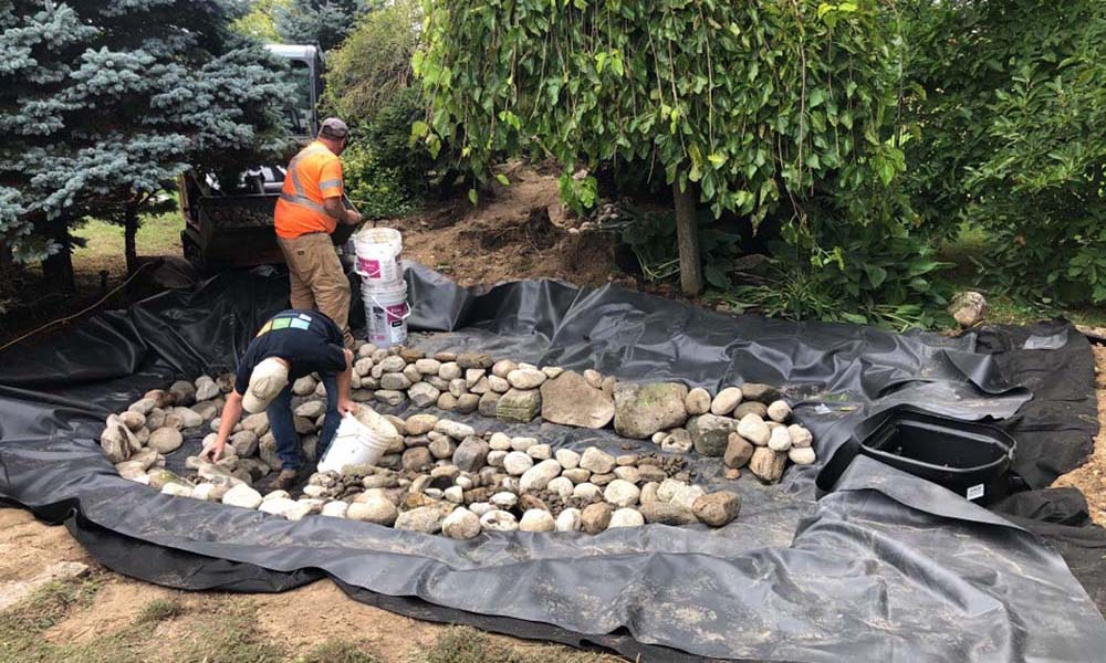 Adding Gravel To A Koi Pond In Kitchener